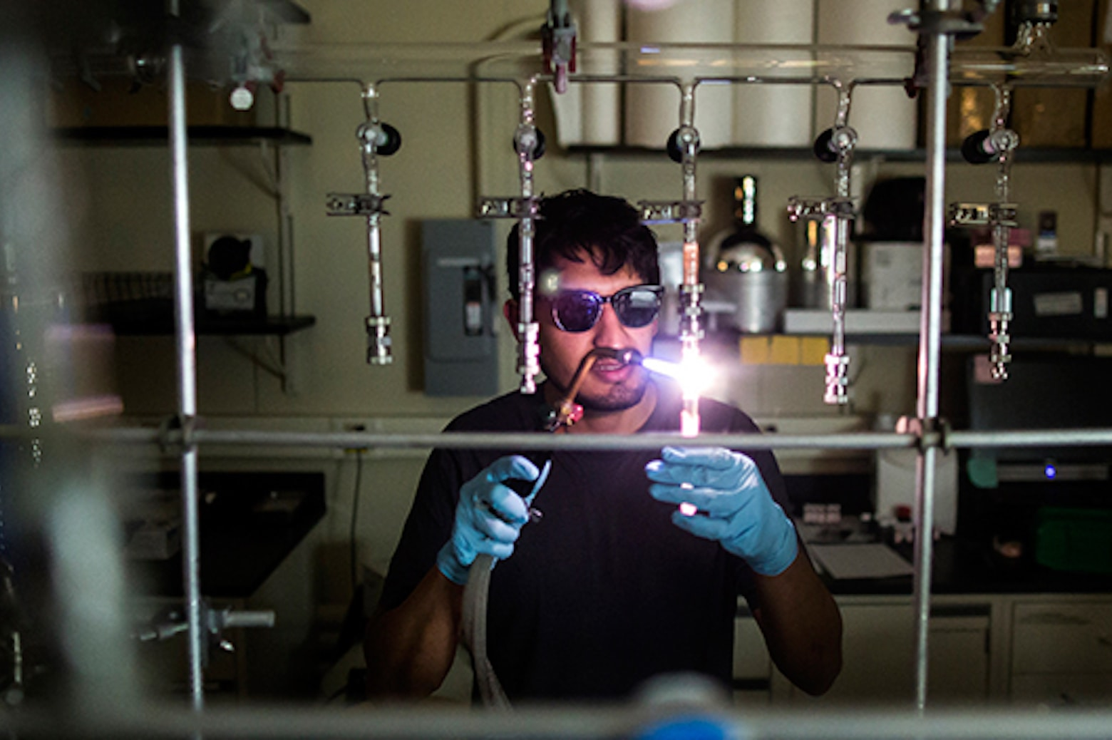 MSE PhD student Juan Lopez cuts a glass tube