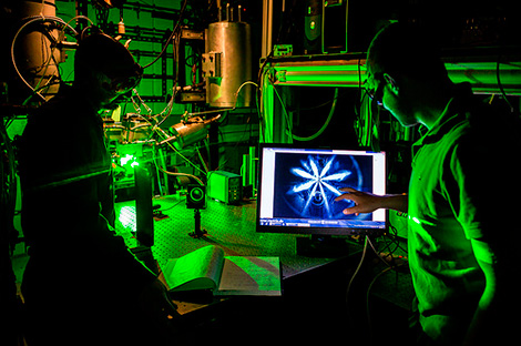 Two scientists work in a lab illuminated by green light