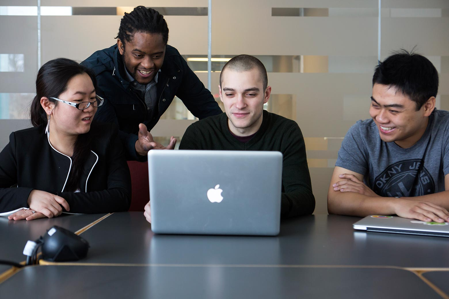 Professors and student gather around a computer