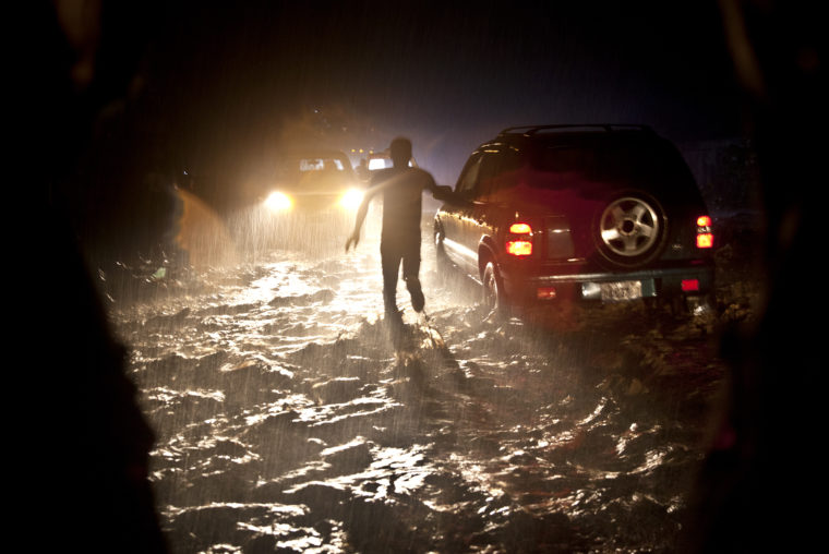A photograph of Corinne Joachim-Sanon, IOE Graduate, and her team caught in a major downpour that floods the outskirts of Cap Haitian.