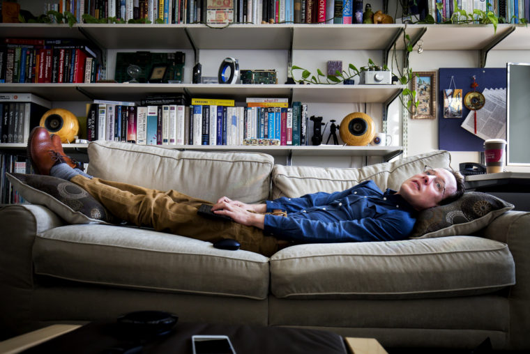 A photograph of CSE Professor J. Alex Halderman stretching out on the couch in his office.
