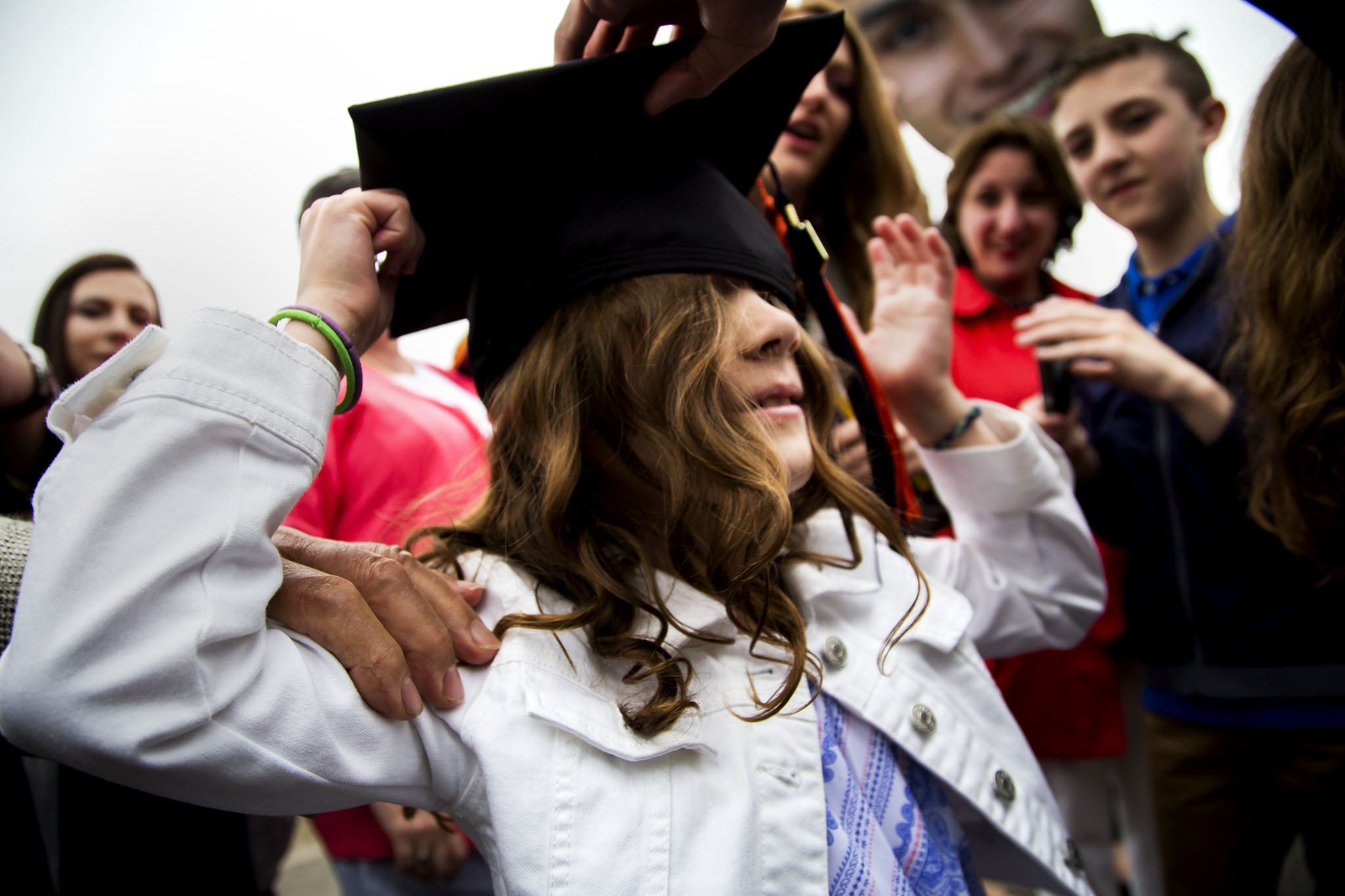 A photograph of a child having a graduation cap put on her.