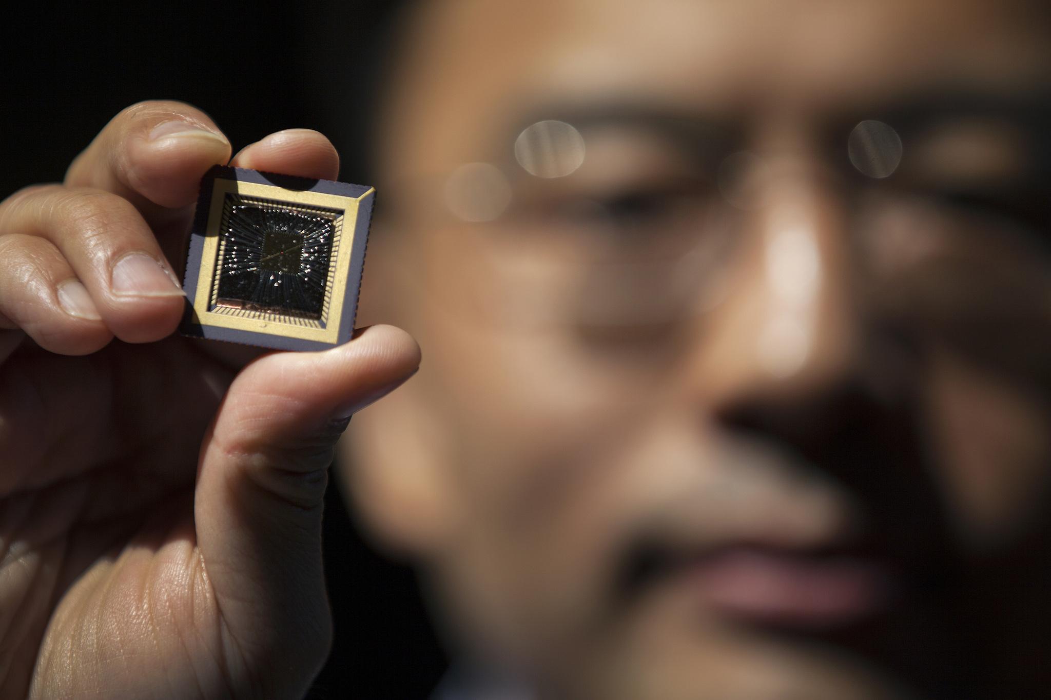 A photograph of EECS Professor Wei Lu holding a memristor chip he created.