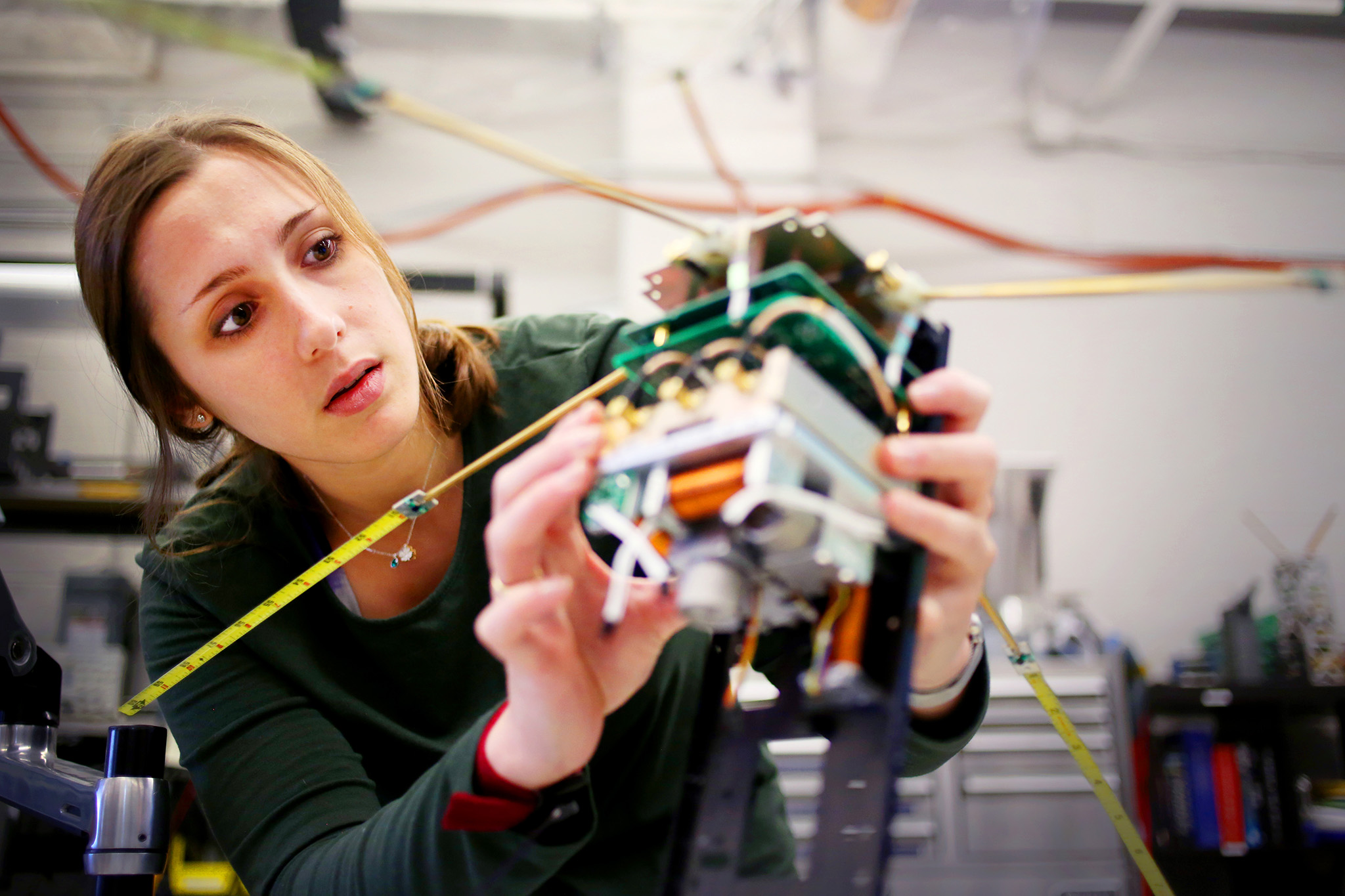 A photograph of a graduate student working with a cube satellite.