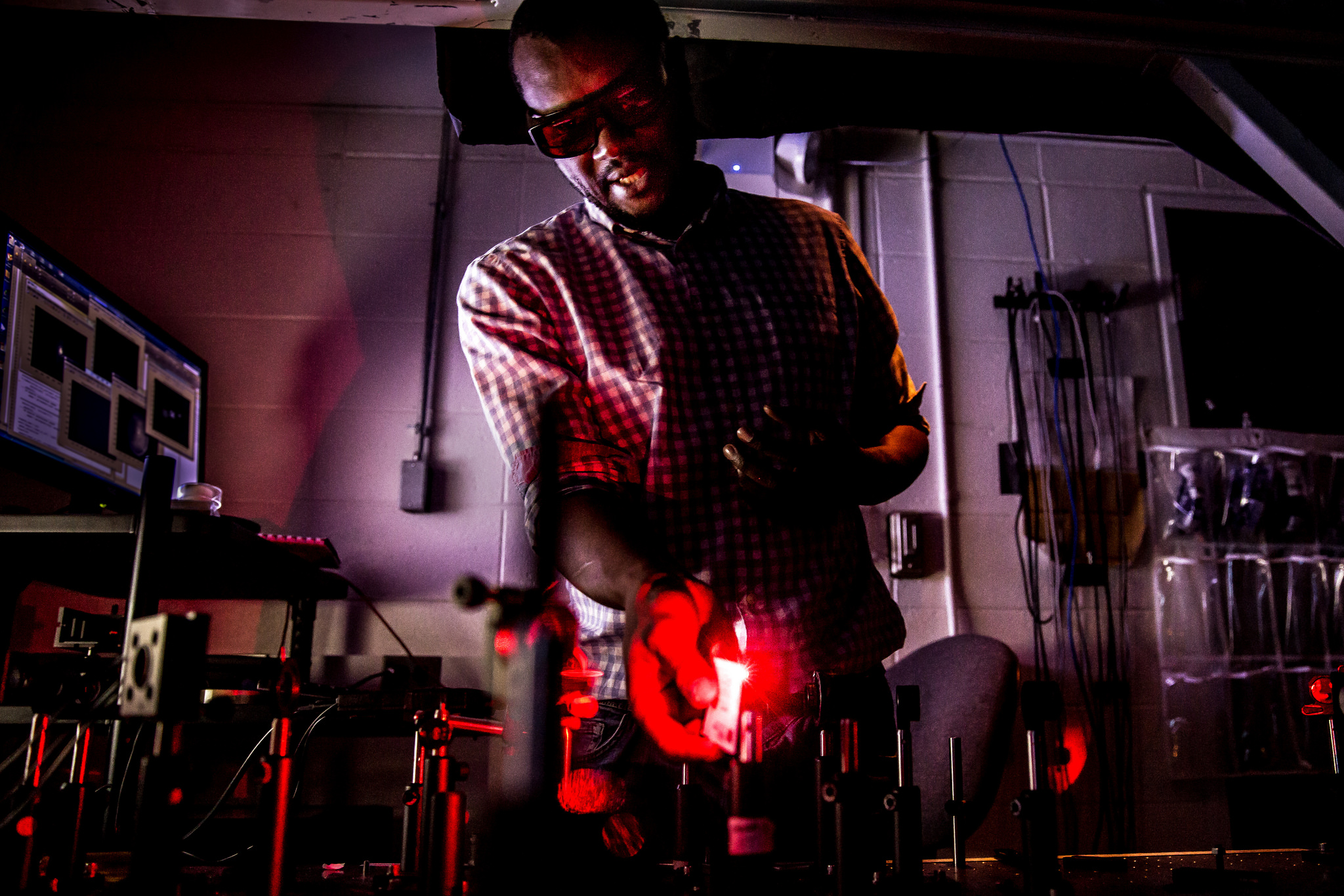 A photograph of EECS Researcher Moussa N'Gom demonstrating use of a laser to focus light through a platelet of yogurt.