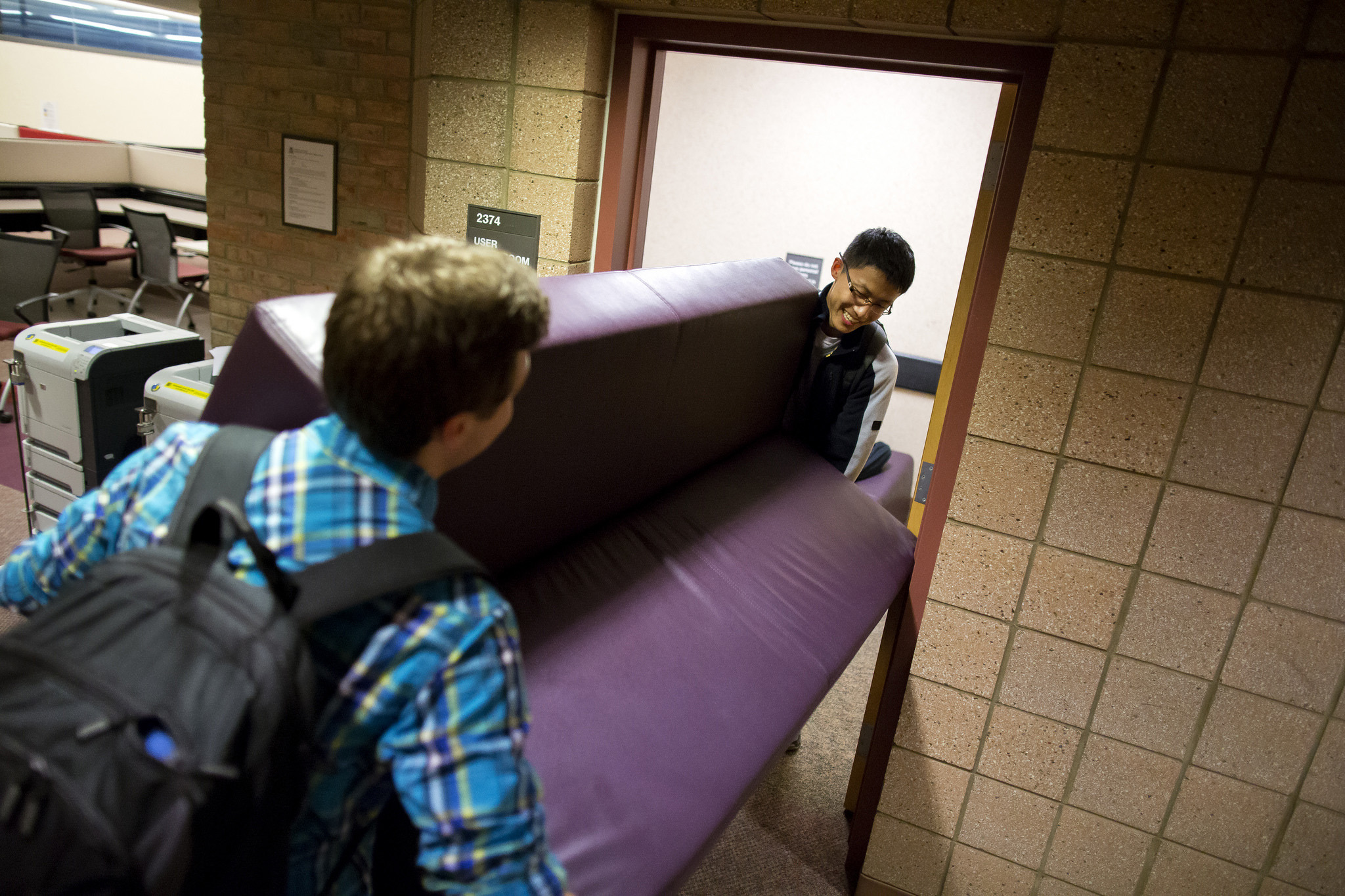 A photograph of students moving a couch into a work room.