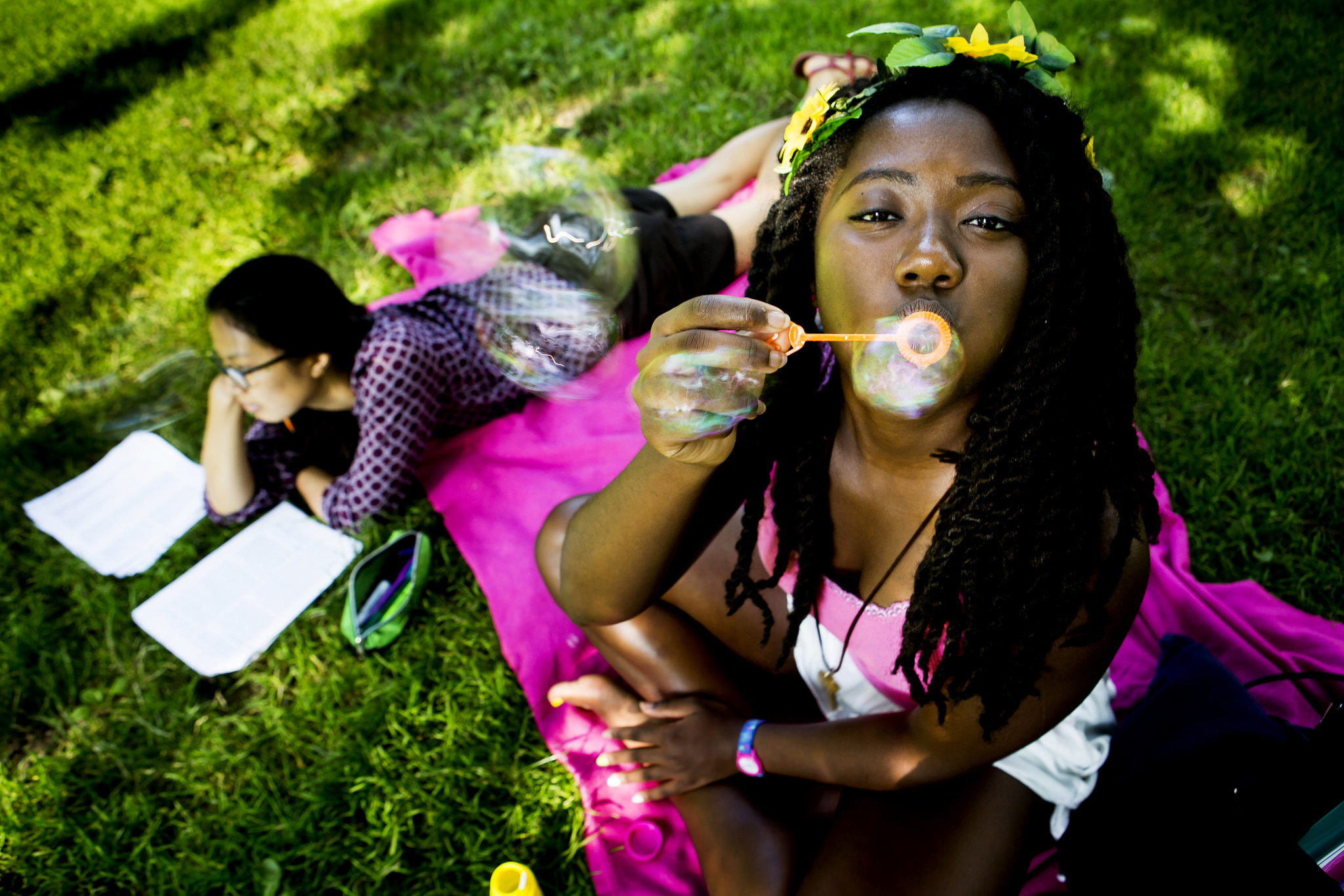 A photograph of a student blowing bubbles.