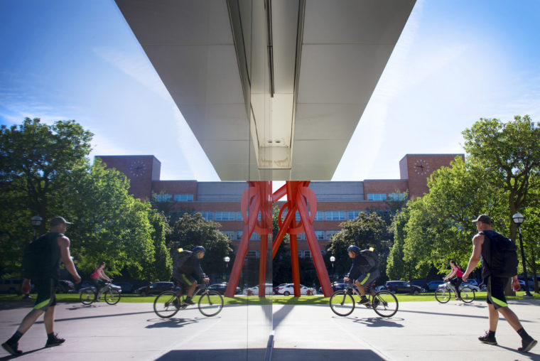 A photo of the reflection of Orion, a steel sculpture on Central Campus through the Museum of Art on Central Campus.