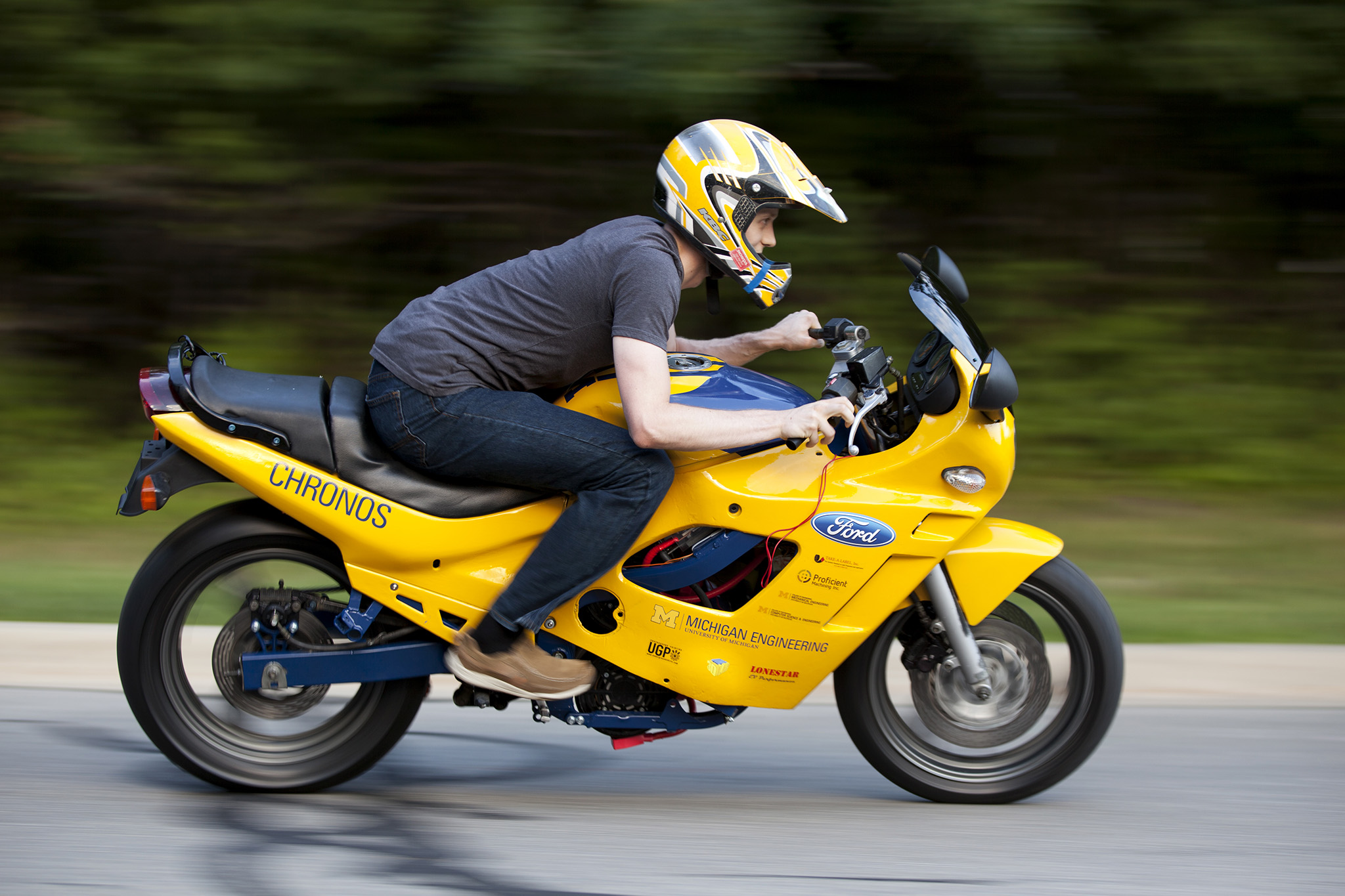 A photograph of a student riding an electric motorcycle.