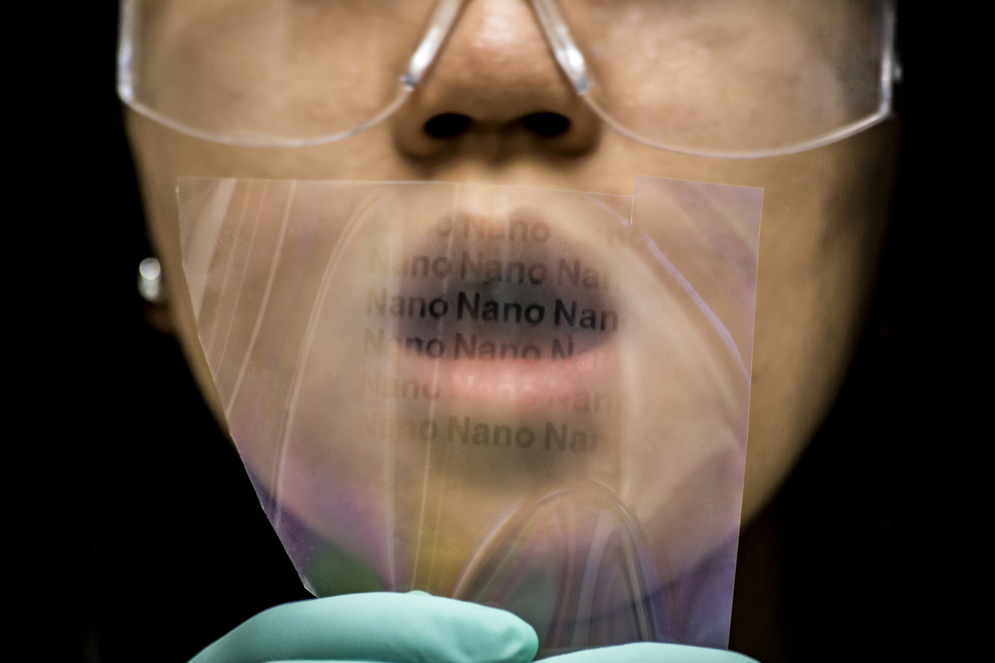 A photograph of a researcher blowing on a film of nanopillars to reveal them.