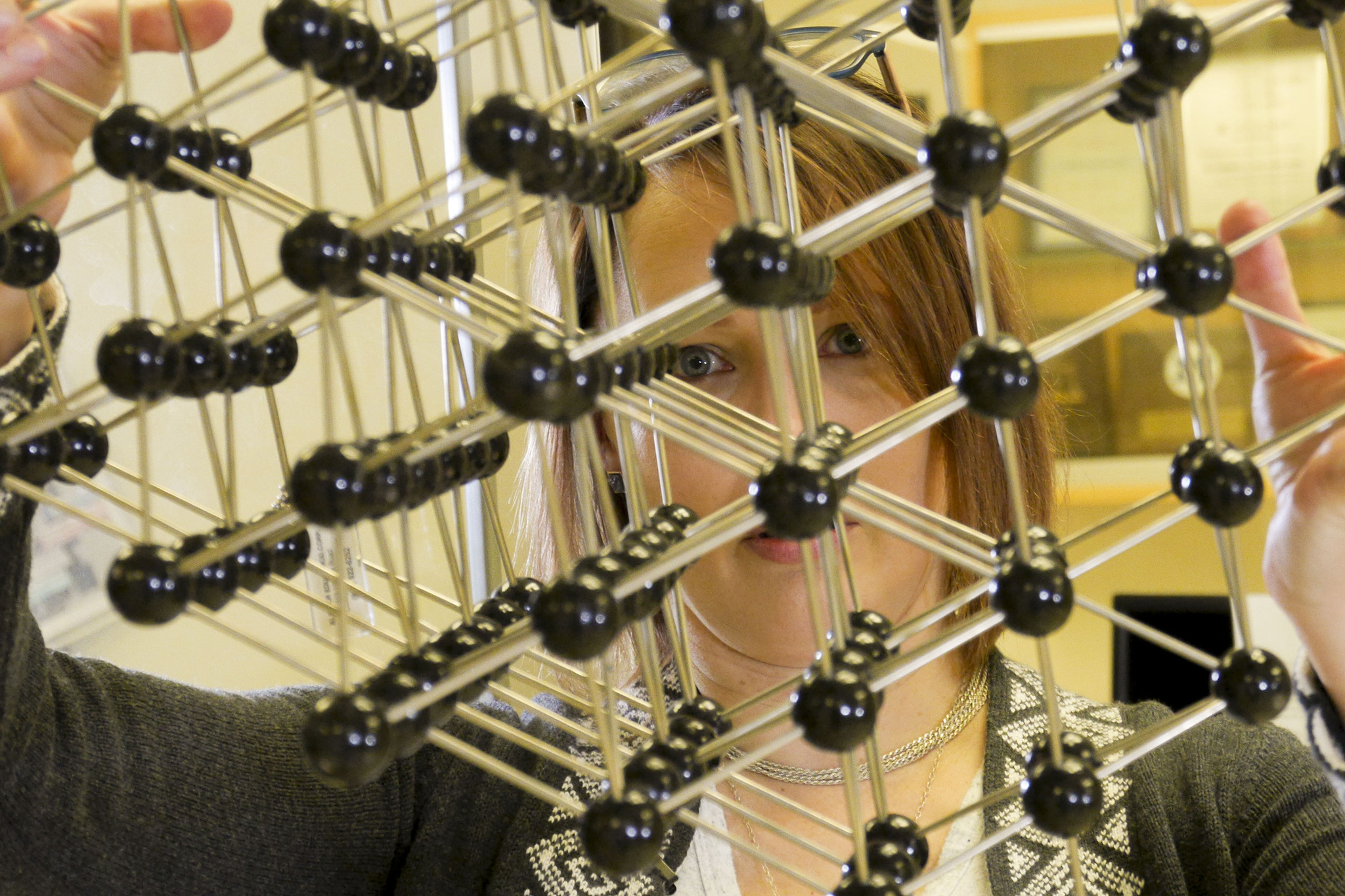 A photograph of MSE Professor Joanna Millunchick holding a crystalline structure.