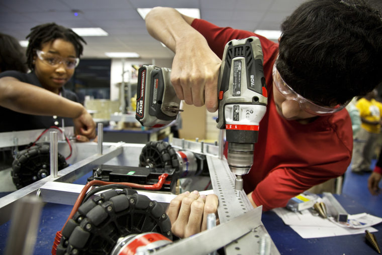 A photo of a high school student working on a robot at the MEZ.