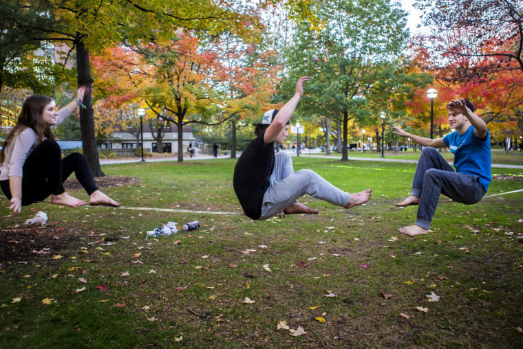 A photograph of students slacklining in the Central Campus Diag.