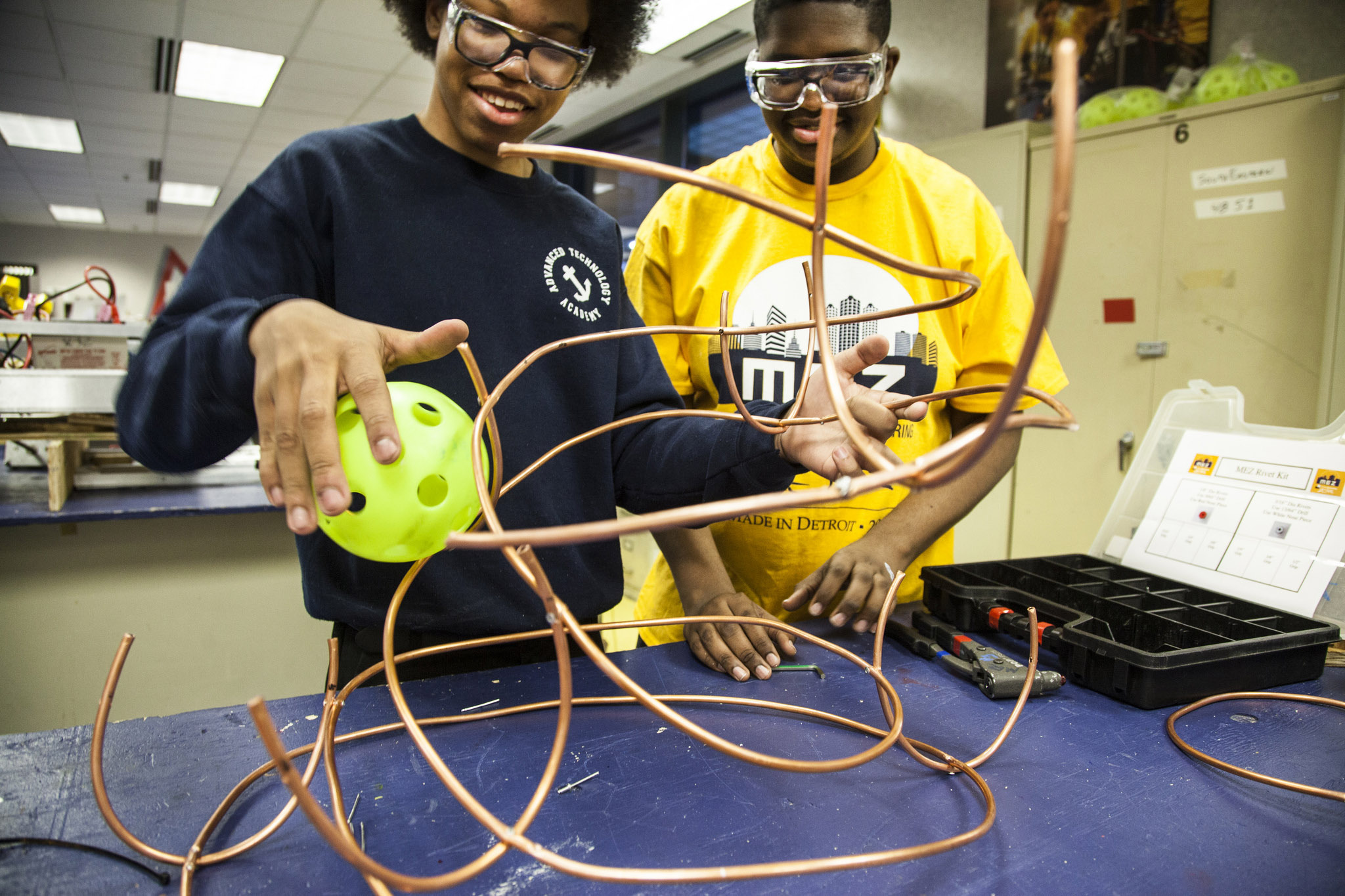 A photography of two high school students hold a whiffle ball next to an elaborate contraption of thin copper piping.