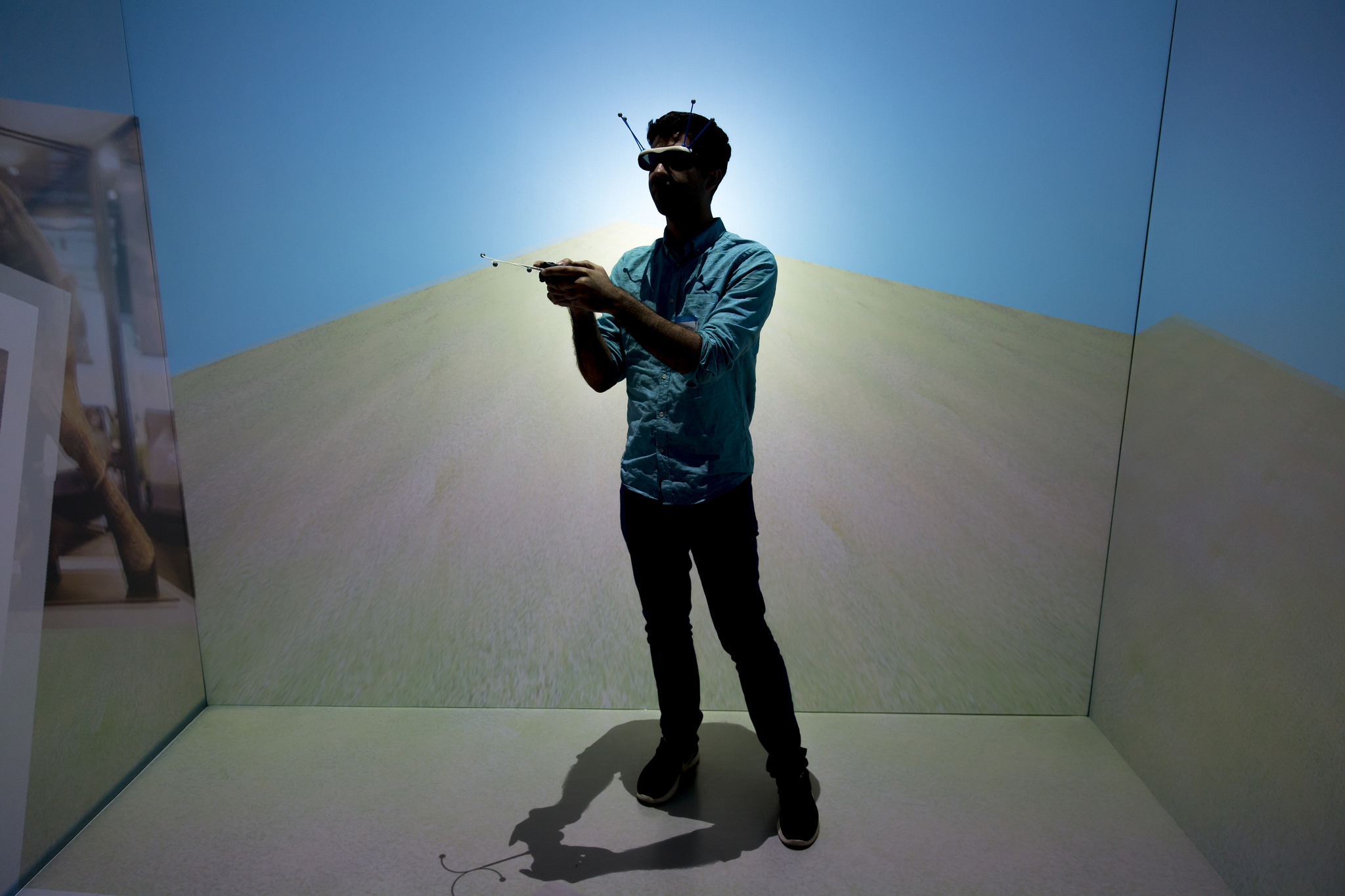 A photograph of a student in silhouette wearing glasses with antennae in a room made of digital projections.
