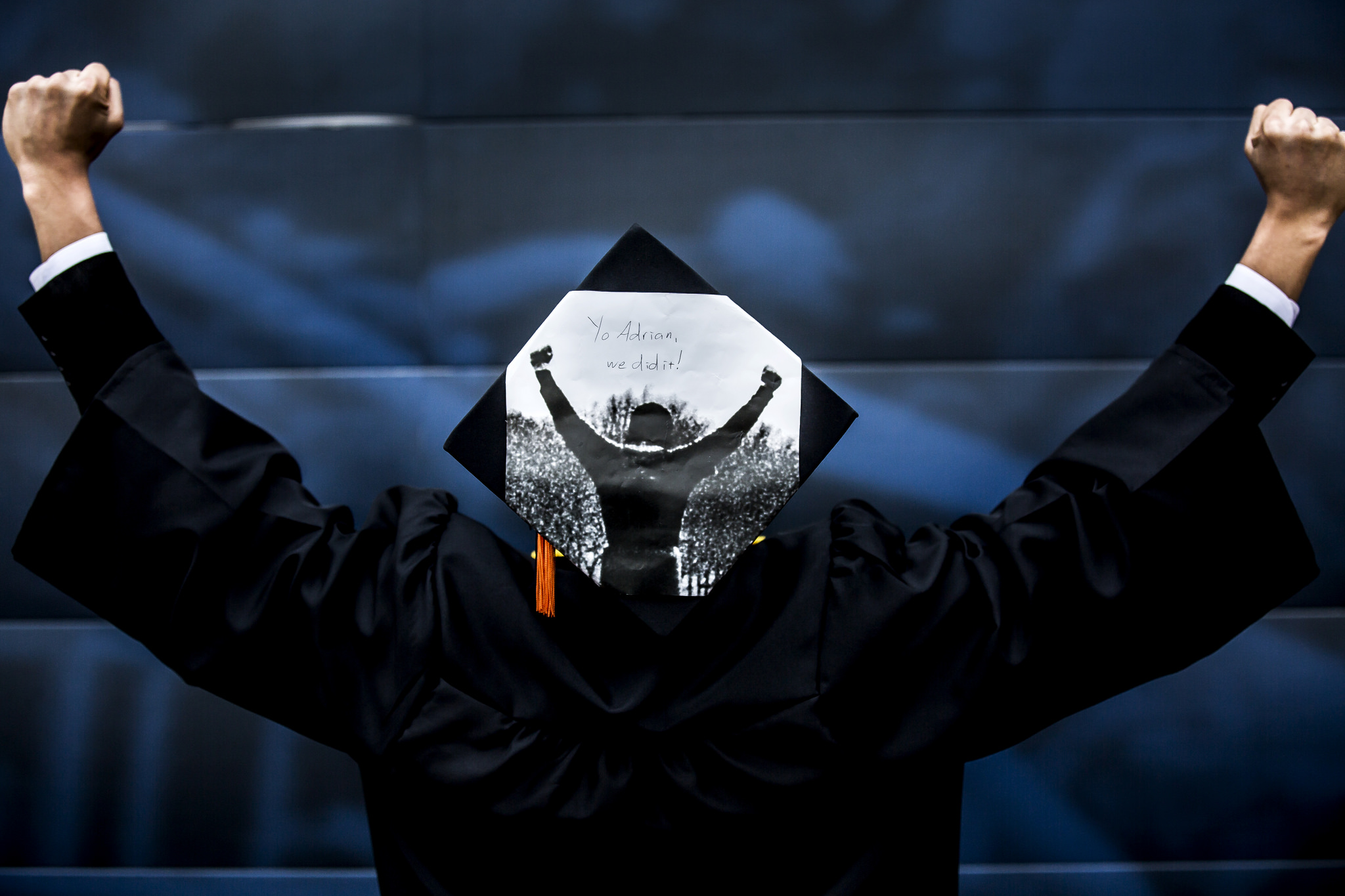 A photograph of a student in his cap and gown immitating the victory pose of Rocky Balboa visible on his cap.