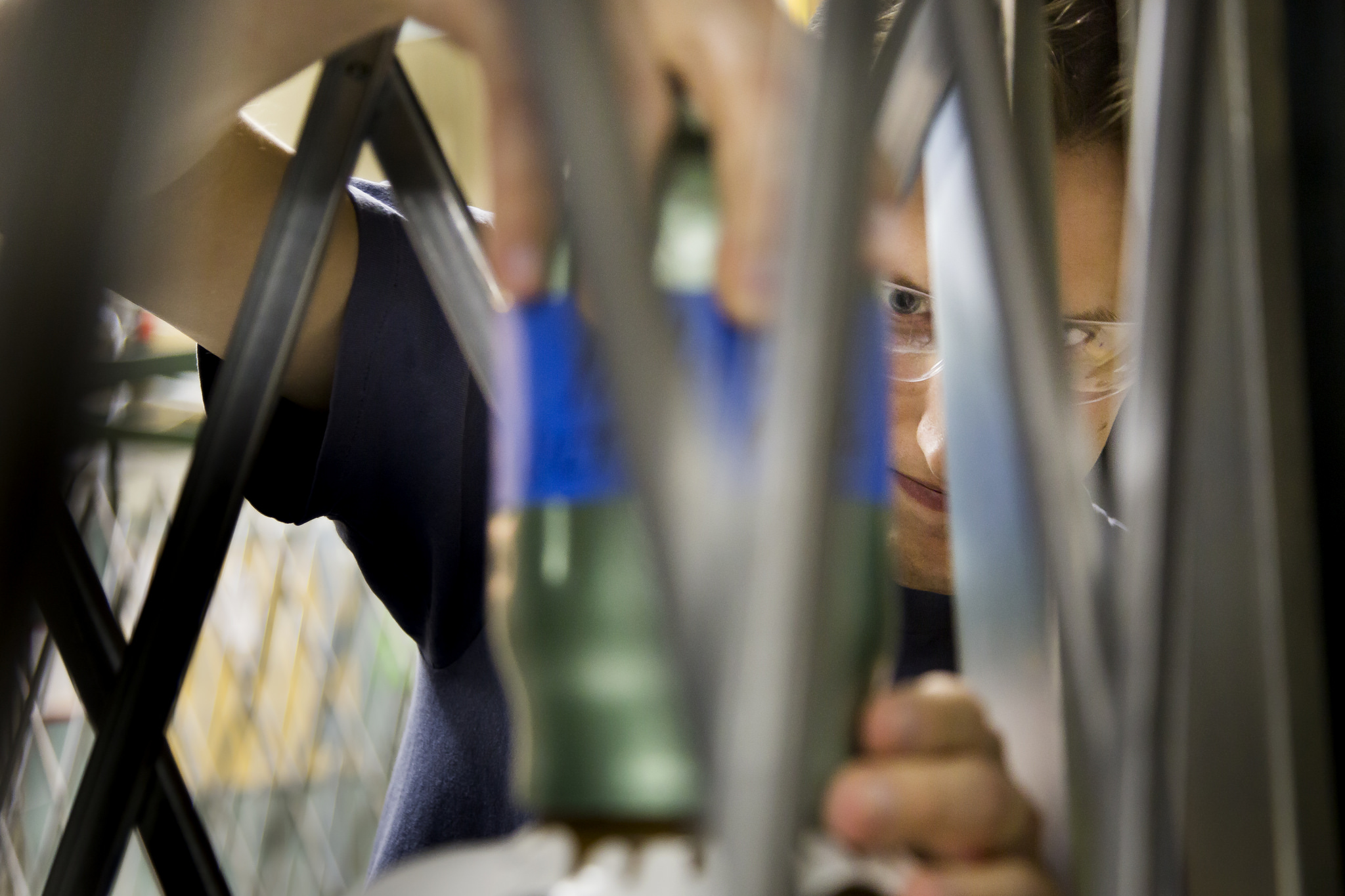 A close-up photograph seen through what looks like a cage of a student handling some sort of cylinder.