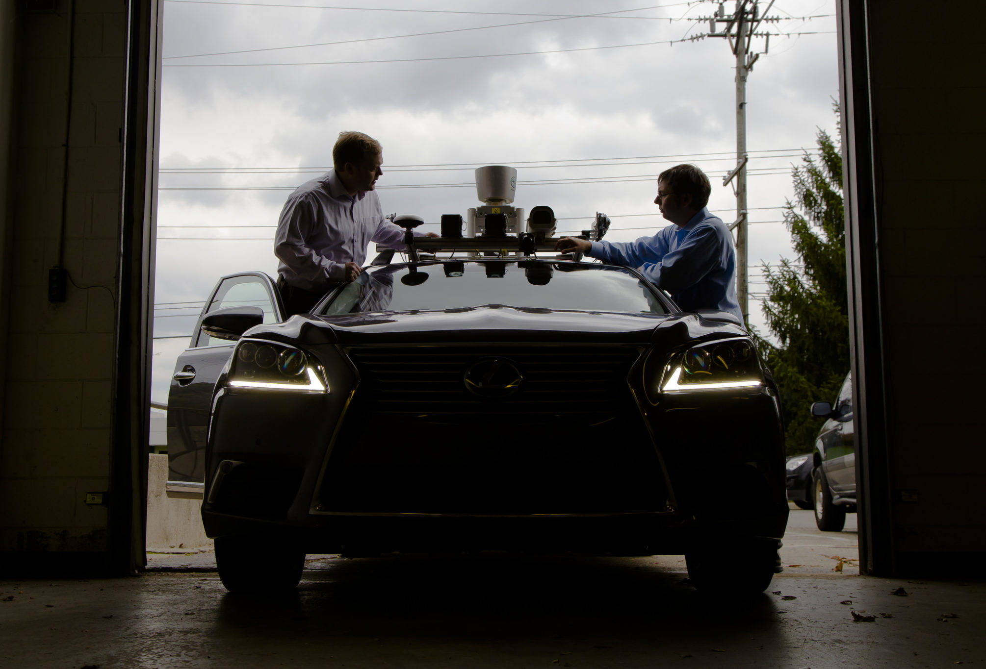 A silhouette photograph of two reseachers standing on either side of a driverless car, with various sensors on top.