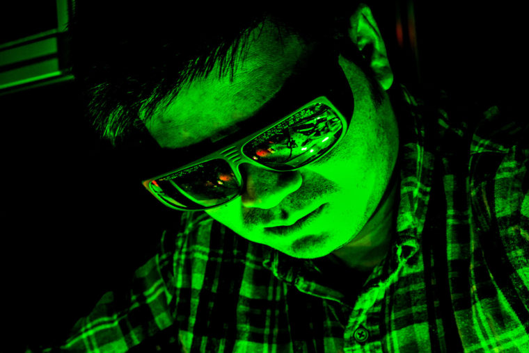 A photograph of a scientist's face glowing bright green with a reflection of his light experiment in his safety goggles.