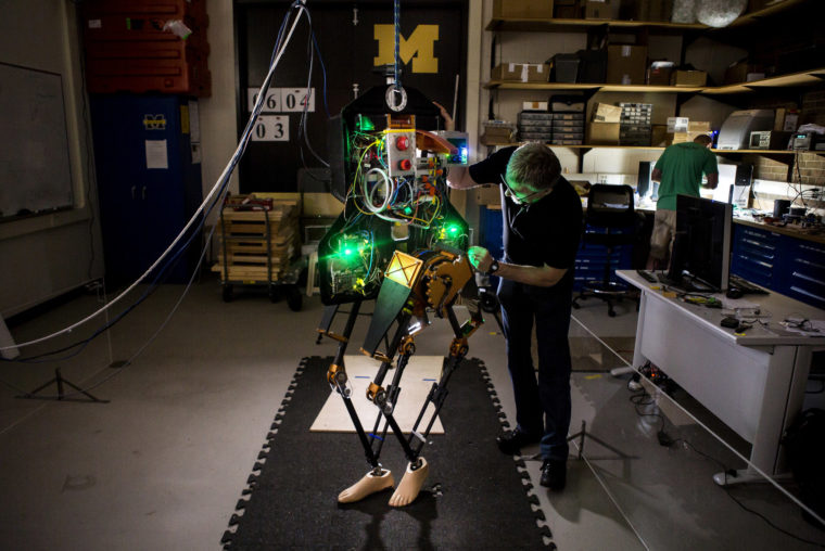 A photograph of Jessy Grizzle next to his bipedal robot, MARLO.