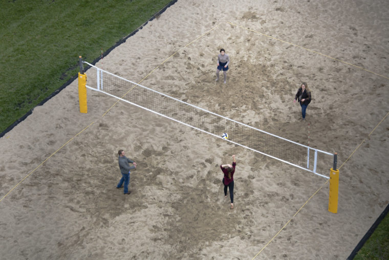A photograph of four students playing sand volleyball as seen from about 4 stories up.