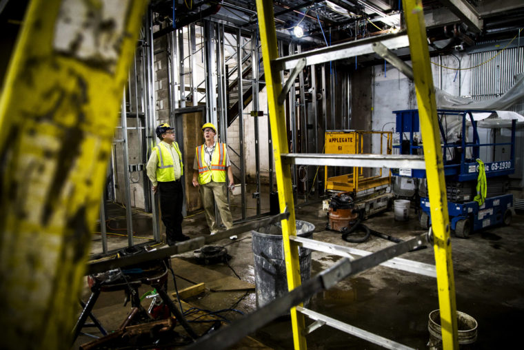 A photograph of two men wearing hard hats and safety vests in a very unfinished university building under renovation.