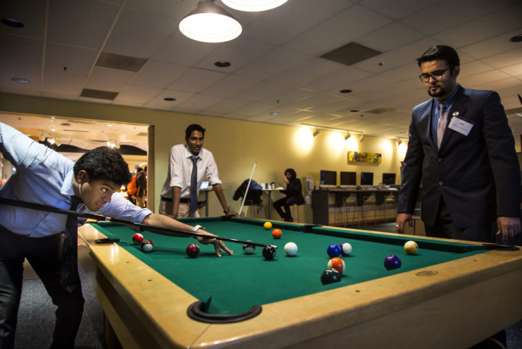 A photograph of three students in business professional attire playing pool in a student lounge.