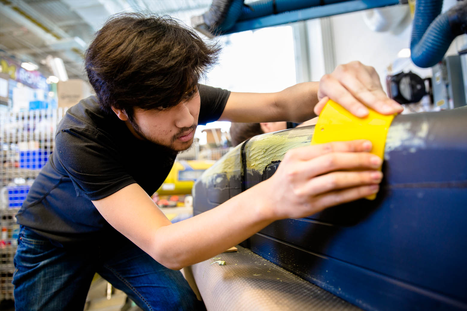 Team member works on a fairing mold for Novum