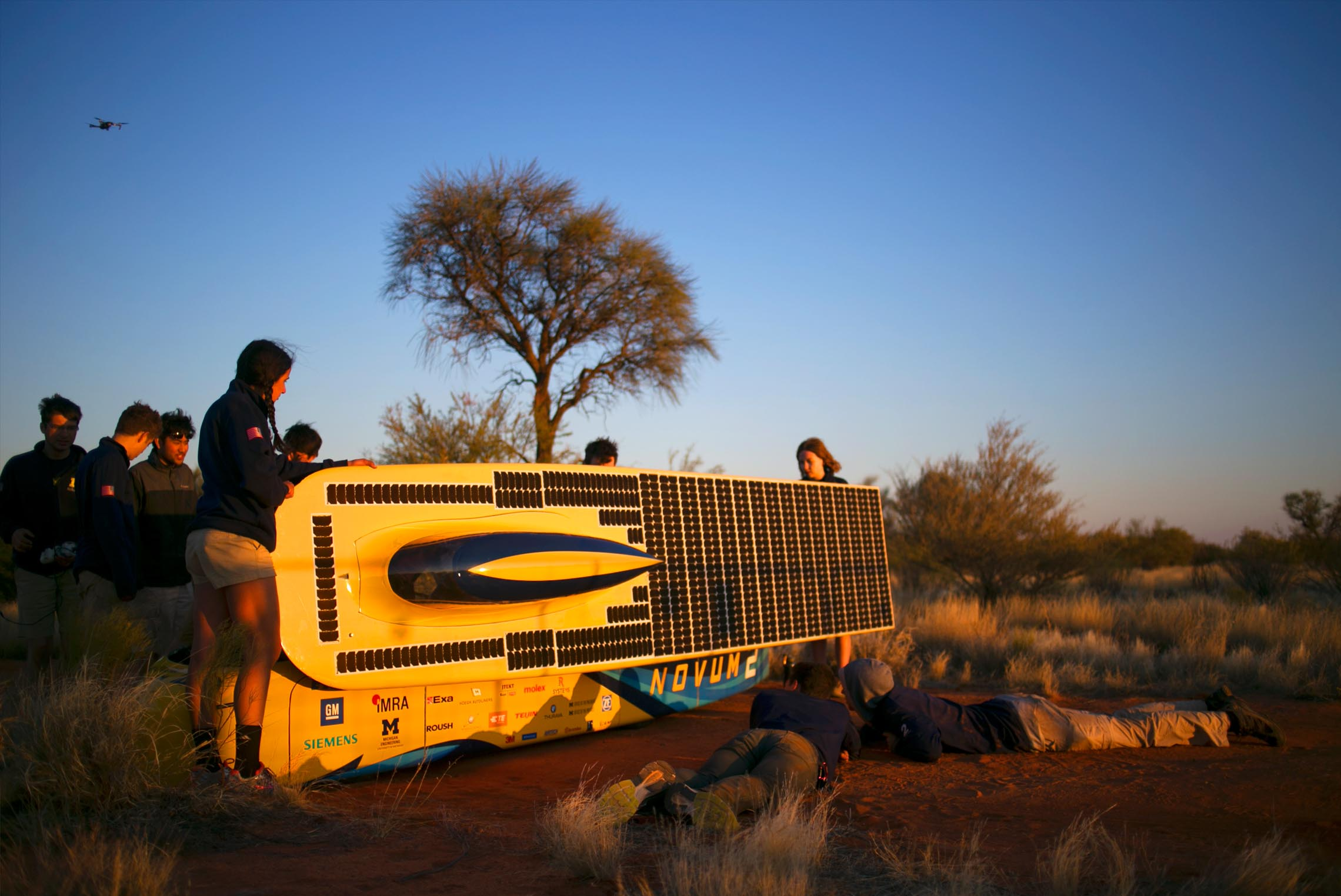 The team charges the car's battery in the setting Australian sun.