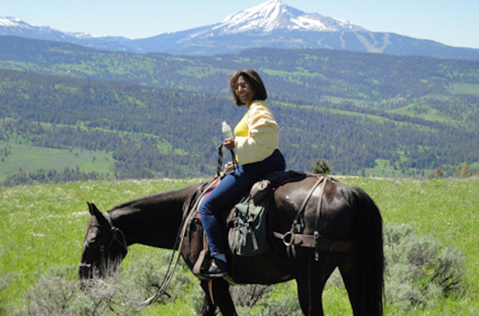 women riding a black horse with a mountain in the background