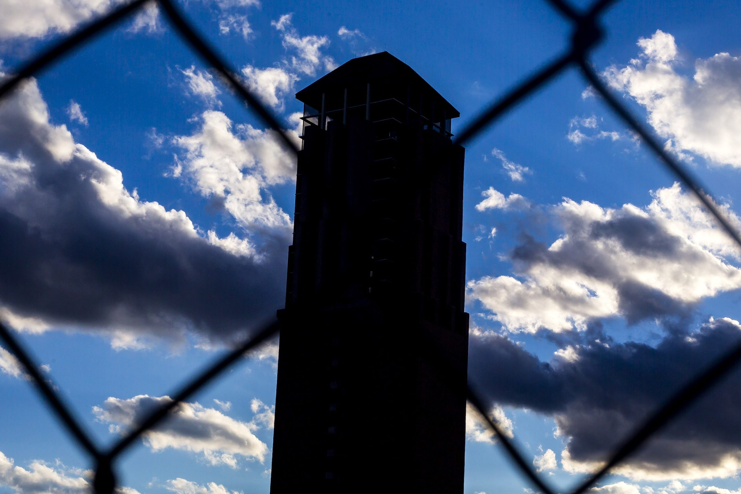 tower behind a fence with clouds in the dark sky