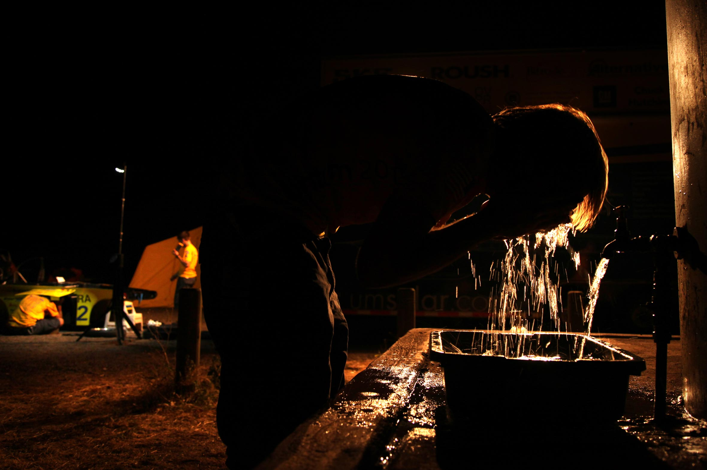 Person leaning over an outdoor water basin splashing water on his face in the dark.