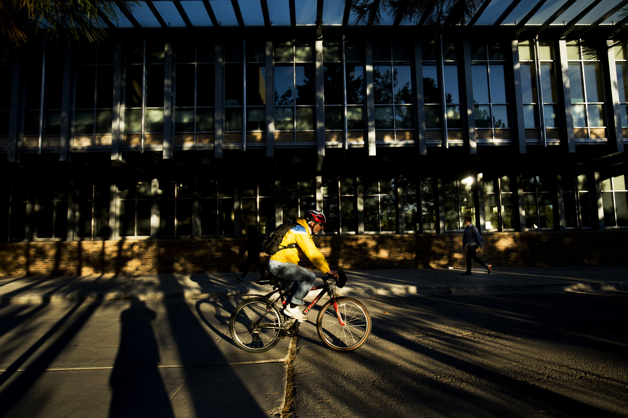 Cyclist rides by the Energy Institute Building