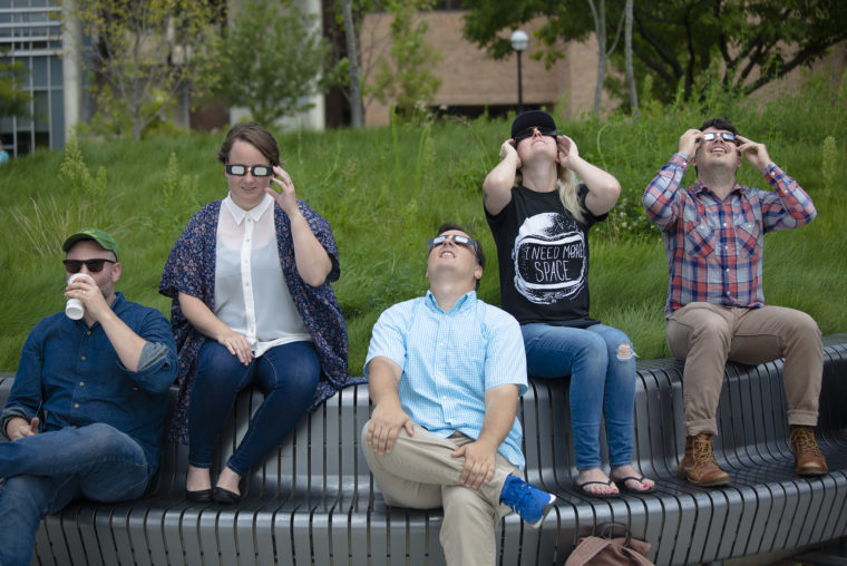 A photograph of students, staff, and faculty looking at an eclipse.
