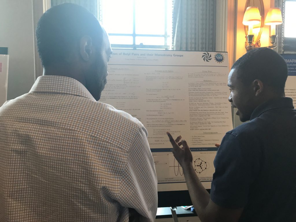 Undergraduate student gesturing to his research poster