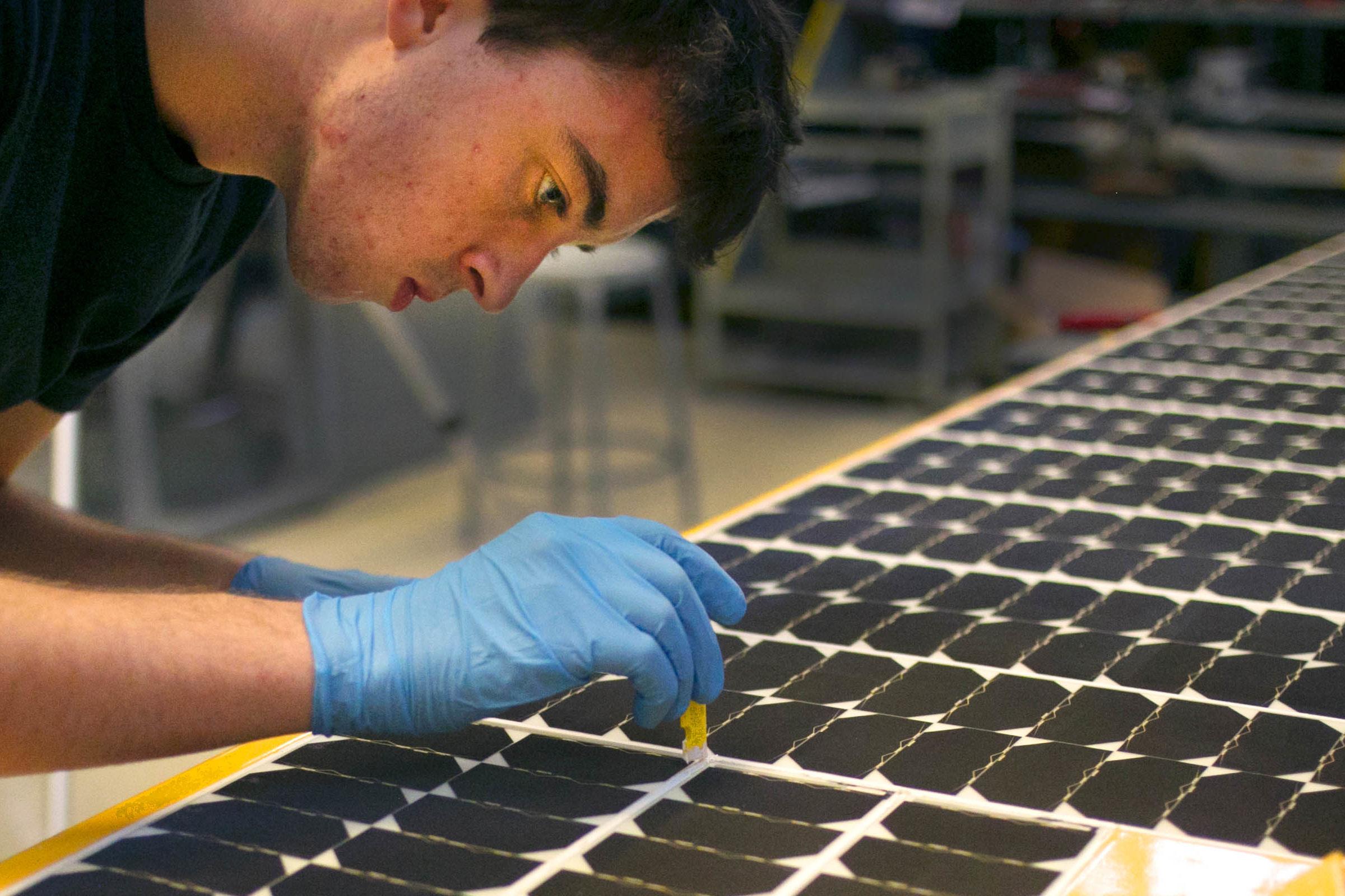 Gluing solar cells to the array canopy.