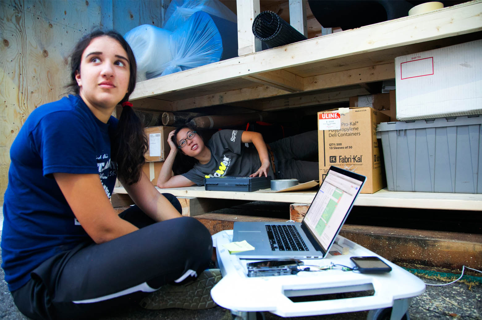 Caroline Subramoney and Janice Lau help pack the shipping container, checking items of the list as they g