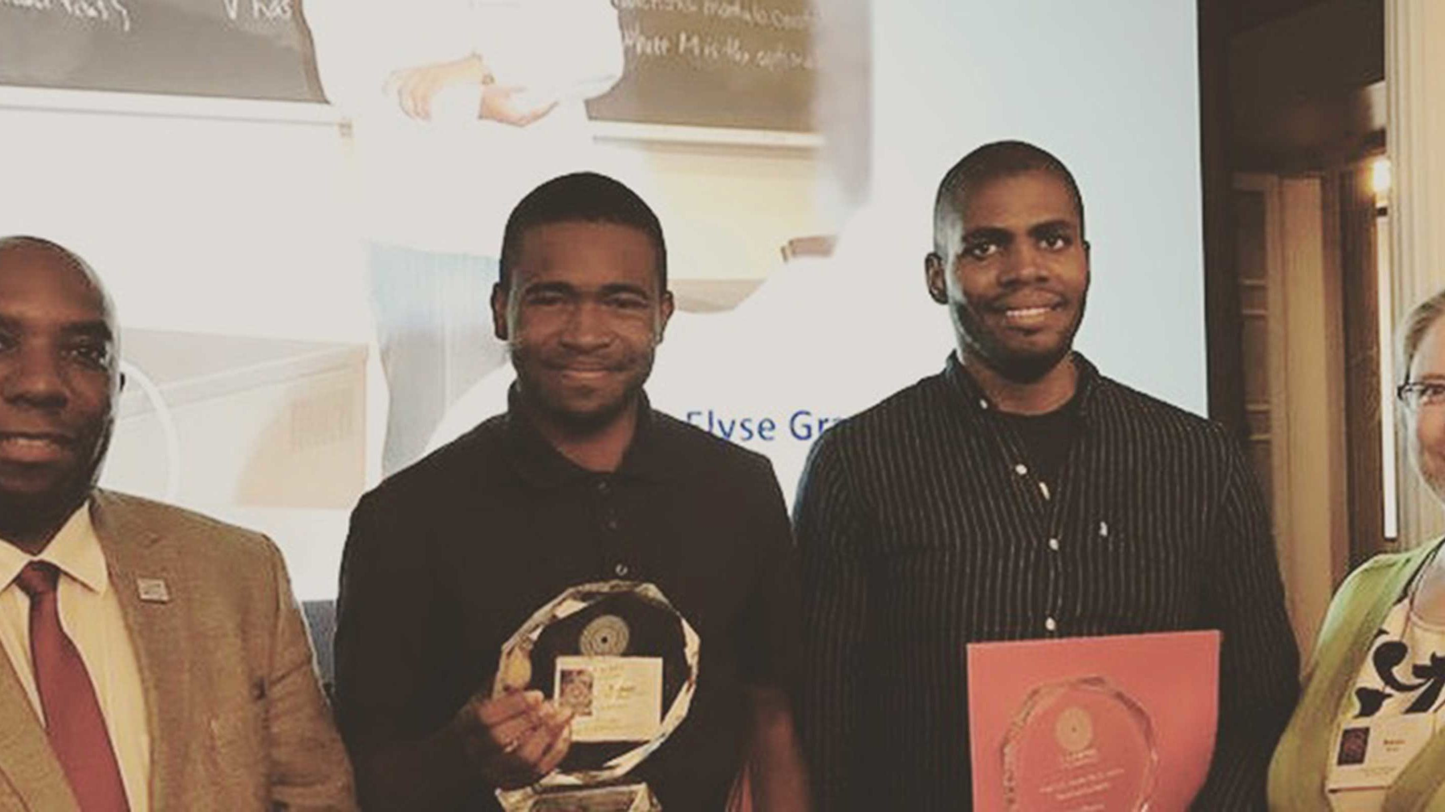 Two graduate students standing with their CAARMS23 awards, smiling next to their advisors.