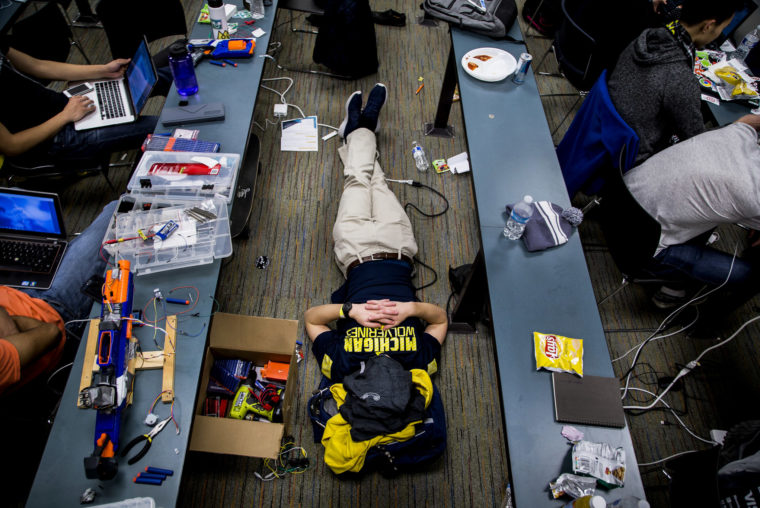 A photograph of a student sleeping on the ground during a hackathon.