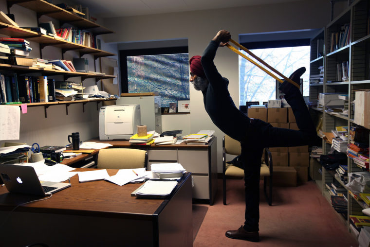 A photograph of a Professor doing yoga.