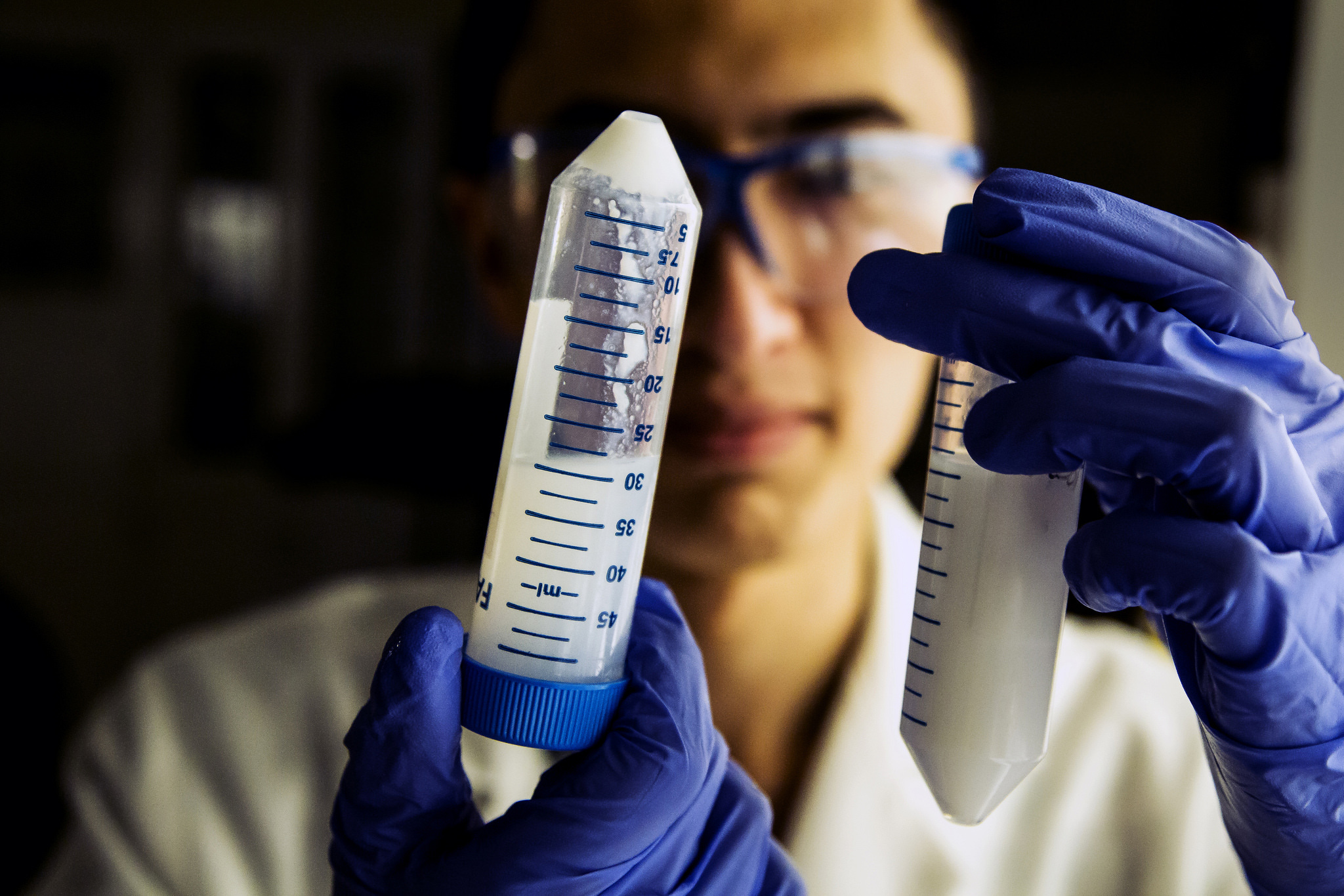 A photograph of a researcher holding a test tube of nanoparticles.