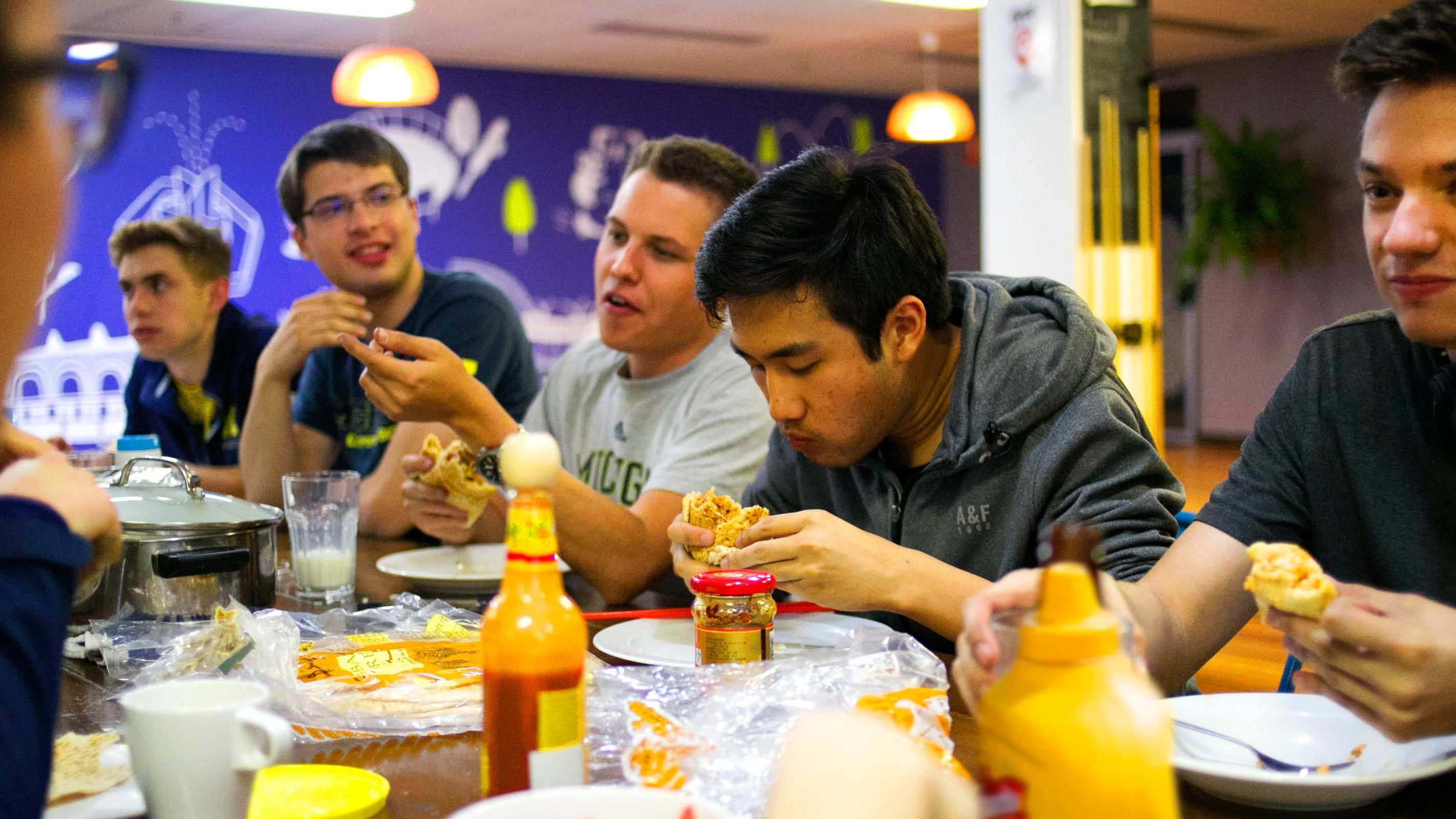 The crew sits down at the hostel dinner table to eat chicken pita wraps.