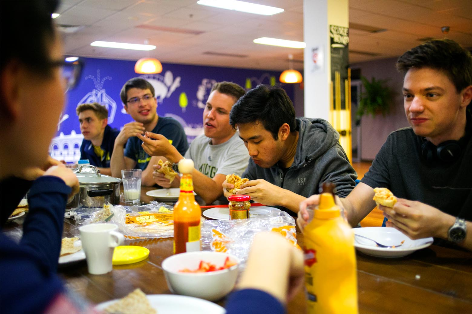 The crew sits down at the hostel dinner table to eat chicken pita wraps