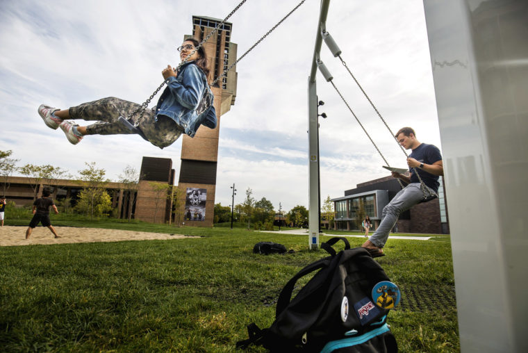 A photograph of students swinging on the Eda U. Gerstacker Grove.
