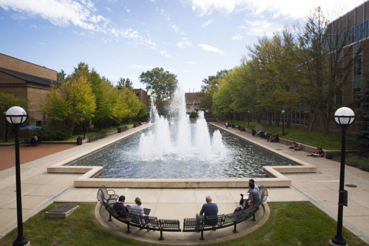 A photograph of a students, staff, and faculty sitting by the Lurie Reflecting Pool.