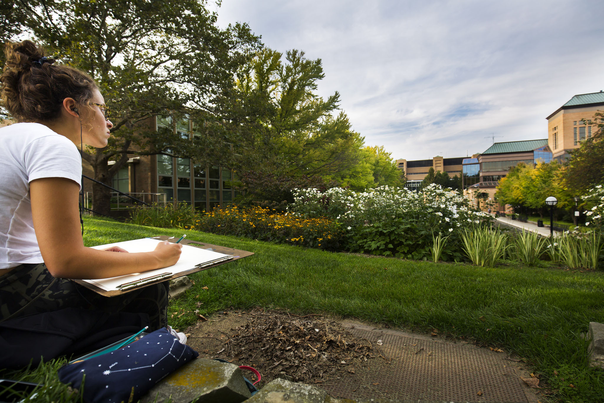 A photograph of a student sketching the Lurie Engineering Center and the Lurie Reflecting Pool.