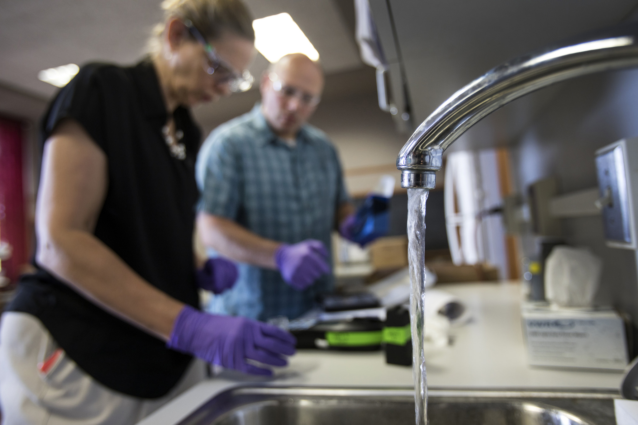A photograph of CEE Professor Nancy Love calibrating an instrument for Flint residents to test their water.