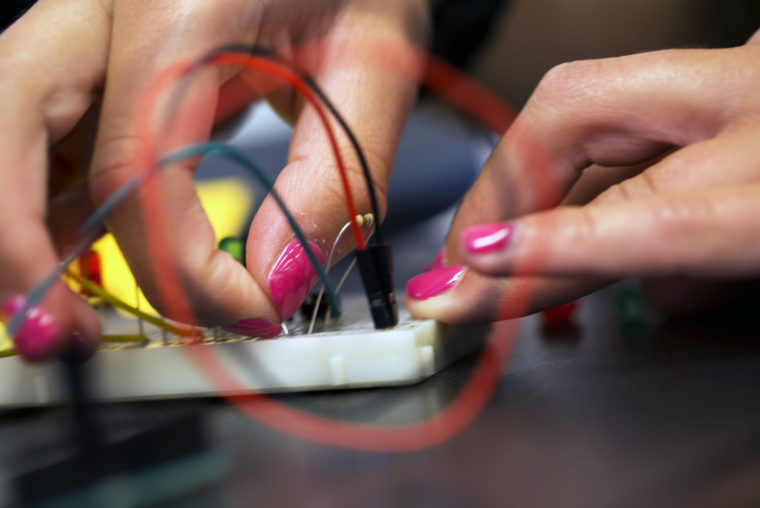 A photograph of a student programming an arduino.