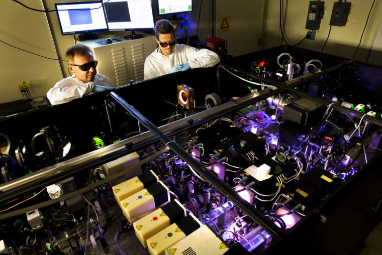 A photograph of researchers testing a laser in lab.