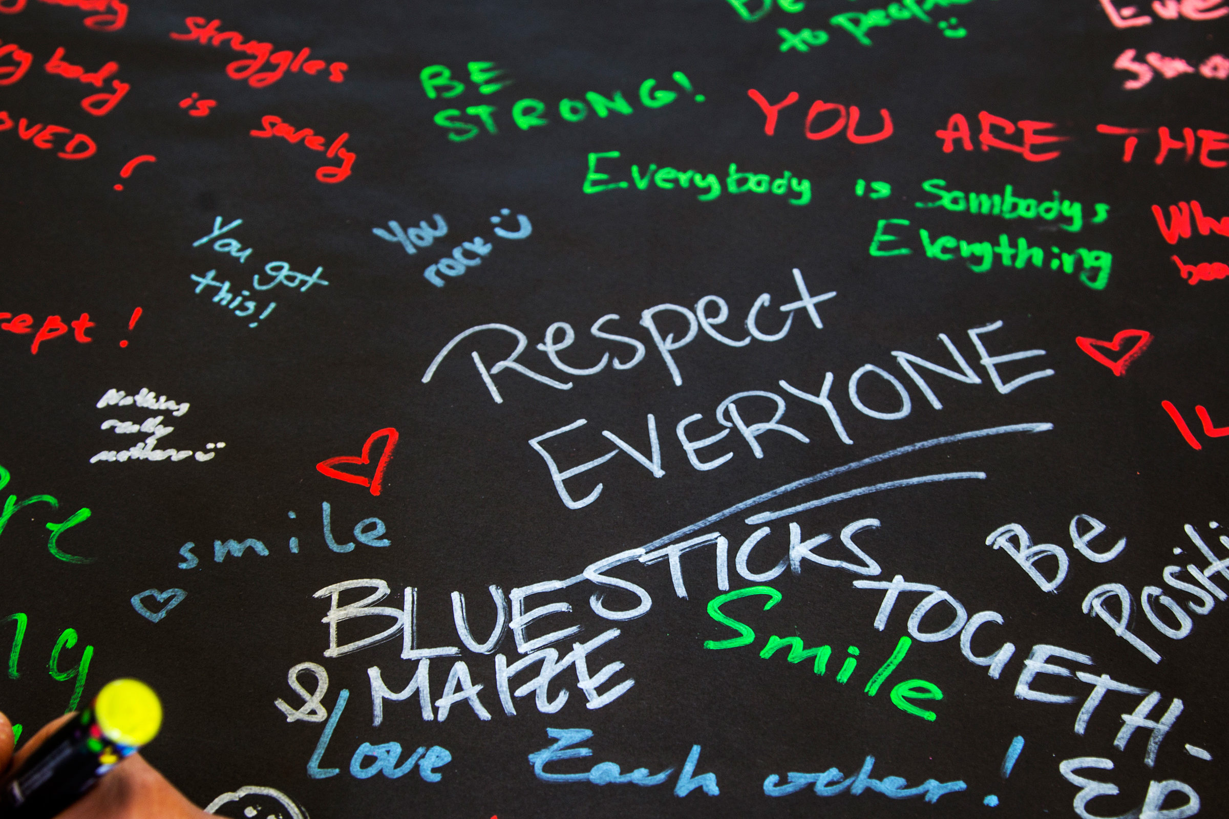 Dozens of colorful messages of positivity written on black paper with a hand holding a yellow marker in the foreground
